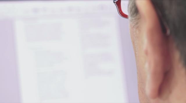 Blick eines Mitarbeiters mit Brille auf ein unscharf auf dem Bildschirm erscheinendes Dokument