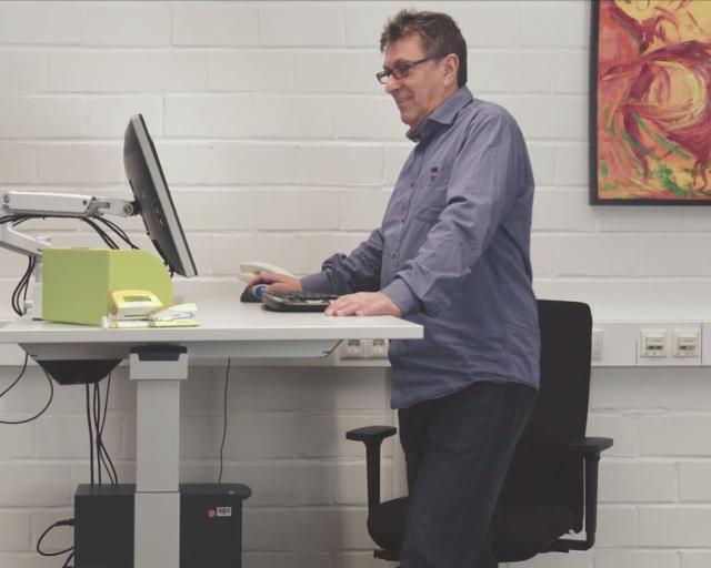 Foto eines älteren Mitarbeiters bei der Computerarbeit an einem Stehtisch