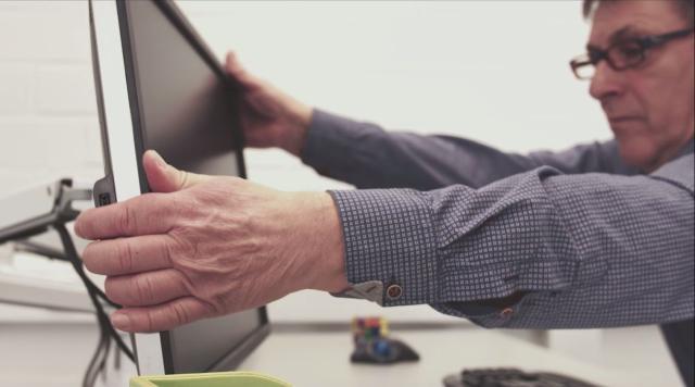 Foto eines älteren Mitarbeiters beim Einstellen der Bildschirmposition